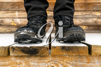 Close-up of a tourist's feet in trekking boots during winter time