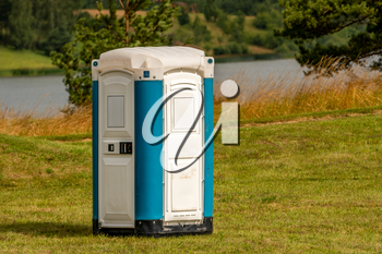 Portable plastic toilet on the meadow with a lake in background