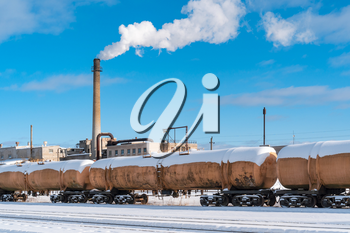 Petroleum waggons on the railroad with factory pipe on background