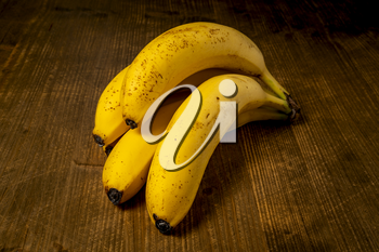 Bunch of Yellow Bananas on Grunge Wooden Background. Close up View