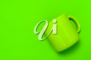 Empty green mug lying on green paper background. Copy space.