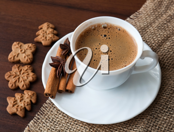 Coffee cup on sacking material with cinnamon stick and cookies