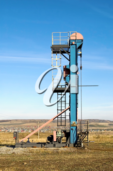 Vertical oil pump swing blue and red against a yellow-brown hills, villages and blue sky