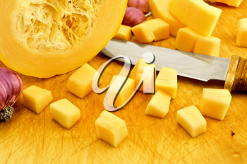 Cut the yellow squash, garlic and a knife on a wooden board