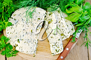 Homemade round cheese with herbs and spices cut into slices, knife on a wooden board with a top