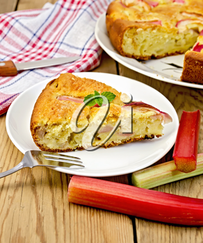 Piece of sweet cake with rhubarb, mint, napkin, knife, fork on the background of wooden boards