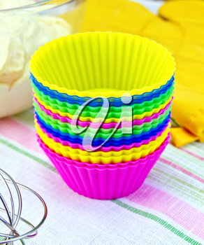 Colorful silicone molds for cakes, mixer, yellow cloth potholder, the dough in a glass bowl on linen background