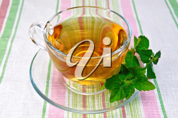 Herbal tea in a glass cup, fresh mint leaves on a background of a linen tablecloth