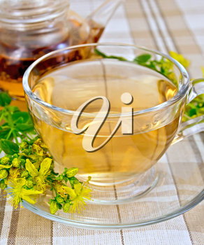 Herbal tea in a glass cup and teapot, fresh flowers tutsan on the linen tablecloth background