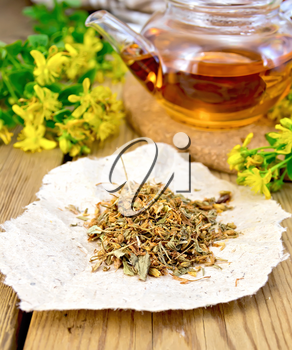 Dried flowers of Hypericum on a piece of paper, tea in the glass teapot and fresh flowers tutsan on the background of wooden boards