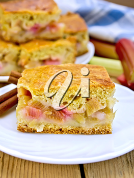 Chunks of sweet cake with rhubarb in a plate, napkin, rhubarb stalks on a wooden boards background