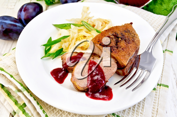 Roasted duck breast with braised cabbage, green onions and plum sauce in a white plate on a towel, plum and fork on the background light wooden boards