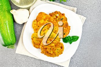 Indian chick-pea flour flatbreads with zucchini and fresh herbs, basil in a plate on a napkin, garlic and oil in a decanter on a background of a granite table top