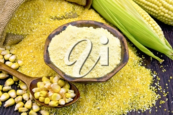 Flour corn in a clay bowl on the grits, cobs and spoon with grains, a bag on a wooden boards background