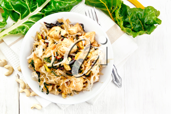 Rice noodles with leafy beet, chicken breast, cashew nuts and soy sauce in a bowl on a towel on wooden plank background
