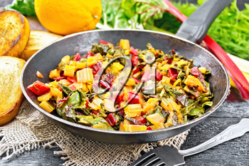 Warm chard salad with orange and onion in a frying pan on sackcloth, bread, fork on a dark wooden board background