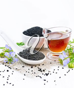 Flour Nigella sativa in a spoon, black cumin seeds in a bowl and oil in gravy boat on burlap, sprigs of kalingi with blue flowers and green leaves on wooden board background