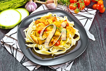 Tagliatelle pasta with meat goulash, tomato, zucchini and thyme in a plate on towel, garlic, spicy grass on wooden board background