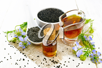 Nigella sativa oil in vial and gravy boat, seeds in a spoon and black cumin flour in a bowl on burlap, kalingi twigs with blue flowers and green leaves on wooden board background