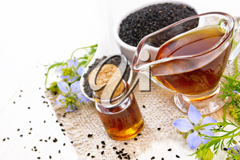 Nigella sativa oil in vial and gravy boat, seeds in a spoon and black cumin flour in a bowl on burlap, kalingi twigs with blue flowers and leaves on white wooden board background