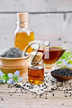 Nigella sativa oil in vial, gravy boat and bottle, seeds in a spoon and black cumin flour in a bowl on burlap, kalingi twigs with blue flowers and leaves on wooden board background