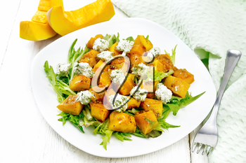 Salad of baked pumpkin, arugula with balls of salt cheese, seasoned with honey, mustard, garlic and vegetable oil in a plate, towel and fork on wooden board background