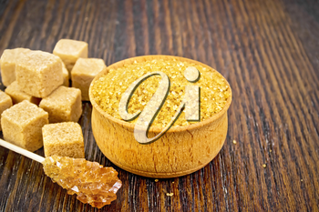 Granulated brown sugar in a bowl, crystalline on a stick and diced on wooden board background