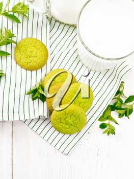 Green mint cookies on a towel with milk in a glass on the background of light wooden board from above