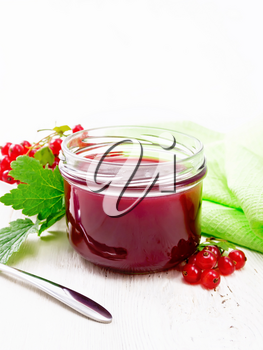 Red currant jam in a glass jar, bunches of berries with leaves, a towel and a spoon on the background of light wooden board