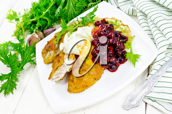Fried turkey breast in breadcrumbs with cranberry sauce, boiled egg, baked parsnip and lettuce in a plate, napkin and fork on light wooden board background