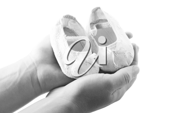 Hands holding newborn baby shoes