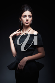 Retro shot of the beautiful young woman in studio. Vintage portrait of pretty girl in 60s style. Gorgeous lady in black dress and pearl necklace against dark gray background