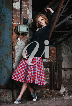 Grunge fashion: portrait of a beautiful young woman in checkered skirt and jacket