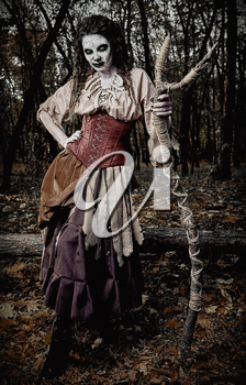 Halloween theme: ugly creepy voodoo witch with staff. Portrait of the evil hag in dark forest. Zombie woman (undead). Grunge texture effect