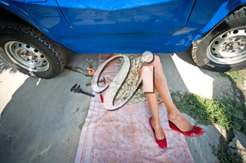Royalty Free Photo of a Vintage Woman With Tools Repairing a Car