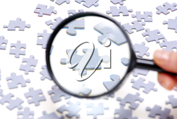 Royalty Free Photo of a Person Holding a Magnifying Glass Over a Puzzle