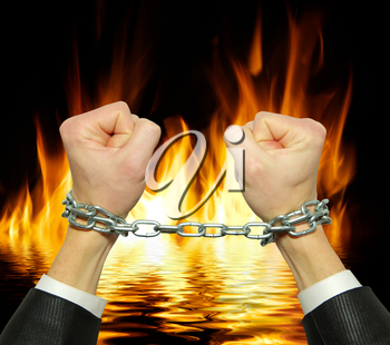 Hands in chains on a fire  background