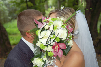 a groom and fiancee kiss after a bouquet horizontal