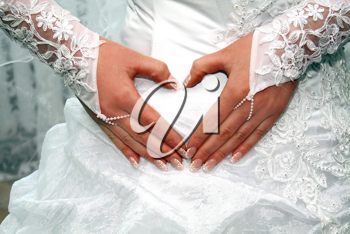 hands of fiancee on a dress as a heart