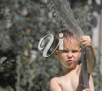 boy squirting water from a hose