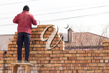 Worker builds a brick wall in the house .