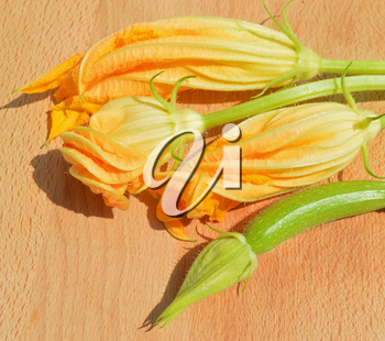 Yellow zucchini blossoms and leaves on wooden cutting board