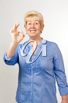 Middle-aged woman shows OK, on grey dackground