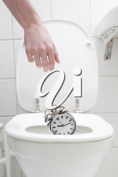 Royalty Free Photo of a Person Throwing Out an Alarm Clock