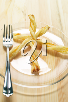 puff pastry sticks on a glass transparent plate over pine wood table
