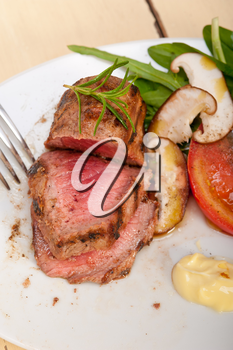 beef filet mignon grilled with fresh vegetables on side ,mushrooms tomato and arugula salad