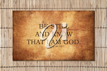 The bible Psalm scripture from 46:10 says Be still and know that I am God. Motivational and encouraging. Strong text over a stone background, with bamboo outside.