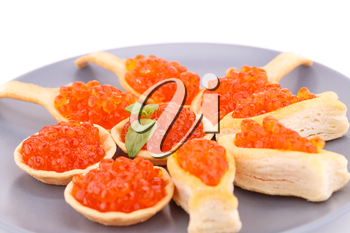 Red caviar in pastries on gray plate.