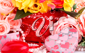 Colorful roses, candles, beads and gift box close up picture.