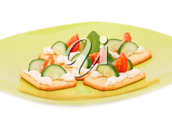 Crackers with fresh vegetables and cream on green plate.